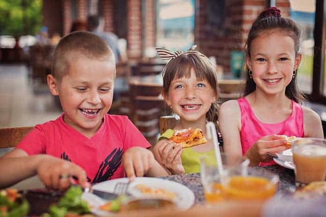 Dzieci w restauracji z radością jedzą posiłek