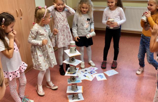 Zajęcia grupowe - dzieci układają wieżę z kubków i kart z obrazkami
